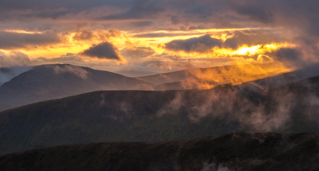 Clouds parted to reveal the last of the sun's rays over the fells to the west